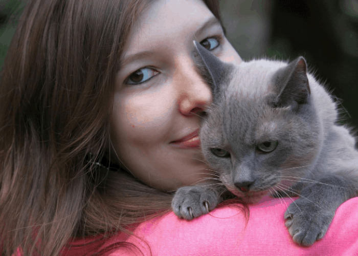 siamese cat being carried by its lady owner