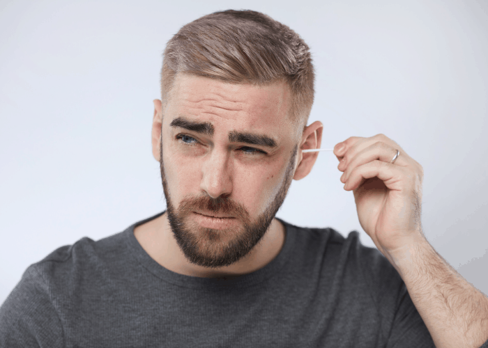man removing his earwax